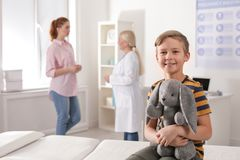 Adorable child with toy and mother visiting doctor stock photography