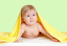 Adorable child under yellow towel. Adorable baby girl under yellow towel Stock Images