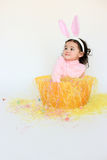 Adorable child wearing bunny ears. Adorable little girl wearing bunny ears while sitting in a basket Stock Images