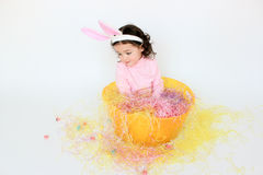 Adorable child wearing bunny ears. Adorable little girl wearing bunny ears while sitting in a basket Stock Photos