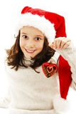 Adorable child wearing Santa Claus hat with a Christmas ball Stock Photos