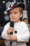 An adorable child 3-years old singing (or talking) into a microphone. Stock Photo