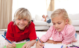 Adorable children drawing lying on the floor Stock Photo