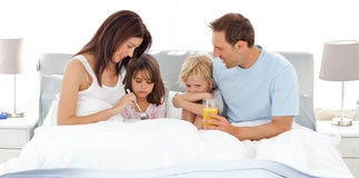 Adorable children having breakfast on the bed Stock Photos