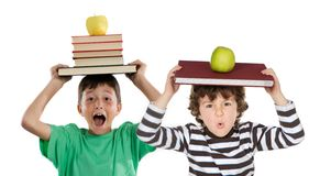 Adorable children with many books and apple. On the head isolated over white Stock Photos