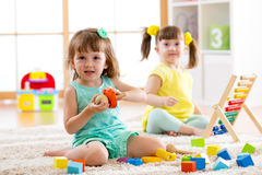 Adorable children playing colorful toys Stock Photos