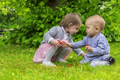 Adorable children playing in the park. Two little girls playing with fruit in the garden Stock Photo