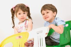 Adorable children sitting on colorful  chairs Royalty Free Stock Photography