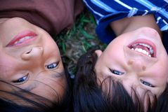 Adorable children together. Two children laying in the grass together, close up of their happy faces Stock Photography