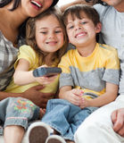 Adorable children watching TV with their parents. In the living-room Royalty Free Stock Photography