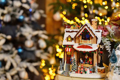 Adorable christmas music toy house with miniature santa presents decorated tree bokeh background Stock Images