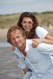 Adorable couple. Lovely young couple doing piggyback ride on a summer day Stock Photography
