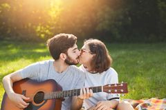 Adorable couple have passionate kiss, spend time outdoor on nature background, play guitar, express perfect romantic relationships. Brunette female kiss with Royalty Free Stock Images