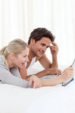 Adorable couple looking at their laptop on the bed Stock Images