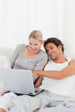 Adorable couple looking at their laptop on the bed Royalty Free Stock Image