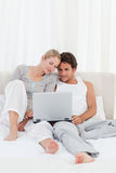 Adorable couple looking at their laptop on the bed Stock Photo
