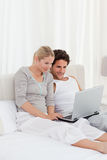 Adorable couple looking at their laptop on the bed Stock Photos