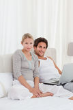 Adorable couple looking at their laptop on the bed Stock Image
