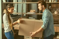 Adorable couple moving apartment together. Do you need some help. Side view on loving young people helping each other with packing stuff while moving new flat royalty free stock photography