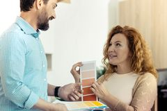 Adorable couple thinking about new design for the house. You choose. Close up of amused wife showing paper with colors for a new design of their house while Royalty Free Stock Images