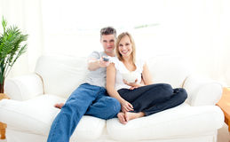 Adorable couple using a remote in the living-room Royalty Free Stock Image