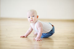 Adorable crawling baby girl. On a floor royalty free stock images