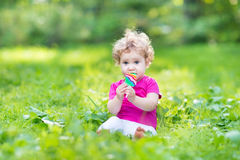 Adorable curly baby girl eating candy in a sunny summer park Stock Photos