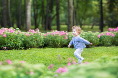 Adorable curly baby girl running in a beautiful park Royalty Free Stock Photos