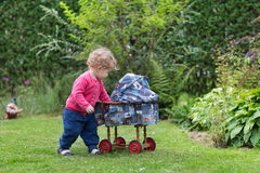 Adorable curly baby girl with vintage toy stroller Royalty Free Stock Photos