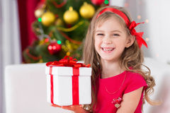 Adorable curly girl with Christmas present Royalty Free Stock Photography