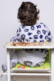 Adorable curly hair boy turned around. Portrait of a cute baby who ate cake making a mess. Royalty Free Stock Photo