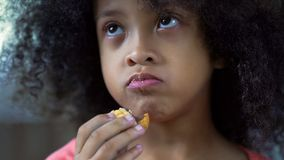 Adorable curly haired girl eating cookie at home, child snacking close-up. Stock photo stock photography