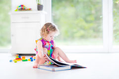Adorable curly toddler girl reading a book Stock Photography