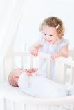 Adorable curly toddler girl talking to newborn brother Stock Photos