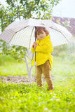 Adorable curly toddler girl wearing yellow waterproof coat holding big adult umbrella uder the pouring rain stock image