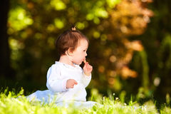Adorable cute baby girl sitting on green meadow and eating the pastry. Cute baby in the white beauty dress. Horizontal photo. Sunshiny warm day in the city Royalty Free Stock Photos