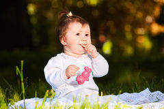 Adorable cute baby girl sitting on green meadow and eating the pastry. Cute baby in the white beauty dress. Horizontal photo. Sunshiny warm day in the city Royalty Free Stock Images