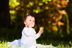 Adorable cute baby girl sitting on green meadow and eating the pastry. Cute baby in the white beauty dress. Horizontal photo. Sunshiny warm day in the city Royalty Free Stock Image