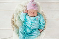 Adorable cute baby girl sleeping in white basket on wooden floor Royalty Free Stock Images