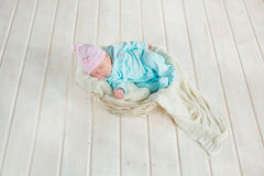 Adorable cute baby girl sleeping in white basket on wooden floor Stock Images