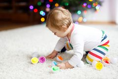 Adorable cute beautiful little baby girl playing with educational colorful shape sorter toy. Adorable cute beautiful little baby girl playing with educational royalty free stock photo