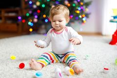 Adorable cute beautiful little baby girl playing with educational colorful shape sorter toy. Adorable cute beautiful little baby girl playing with educational stock photo