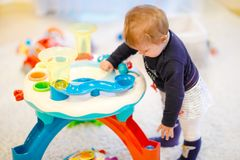Adorable cute beautiful little baby girl playing with educational sorter toys at home or nursery. Healthy happy toddler stock images