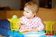Adorable cute beautiful little baby girl playing with educational toys at home or nursery. Happy healthy child having royalty free stock images