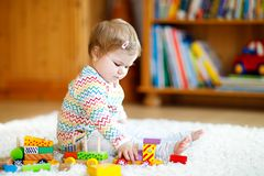 Adorable cute beautiful little baby girl playing with educational wooden toys at home or nursery. Toddler with colorful. Train. Happy healthy child having fun royalty free stock photo