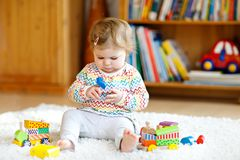 Adorable cute beautiful little baby girl playing with educational wooden toys at home or nursery. Toddler with colorful. Train. Happy healthy child having fun stock images