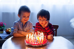 Adorable cute boys, blowing candles on a birthday cake Stock Photo