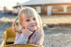Adorable cute caucasian blond kid girl portrait sitting in wooden cart, looking aside and dreaming at farm or park during warm royalty free stock photography