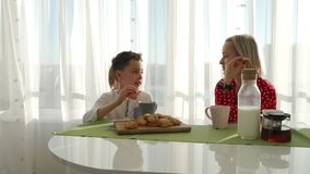An adorable cute caucasian boy is eating cookie beside his young mother with blond hair. Little brother is stealing. Cookies stock video