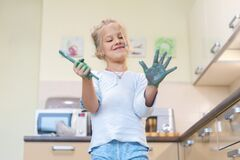 Adorable cute caucasian little blond girl enjoy having fun painting with brush and palm at home indoors on weekend. Cheerful happy